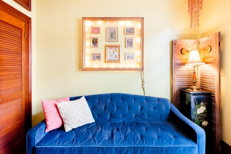 The vibrant blue couch is a cozy place to relax after a long day of exploration