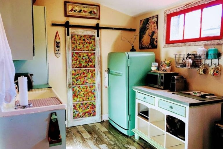 This bohemian styled kitchen is complete with a teal painted fridge and red windowsill. Miami on the cheap.