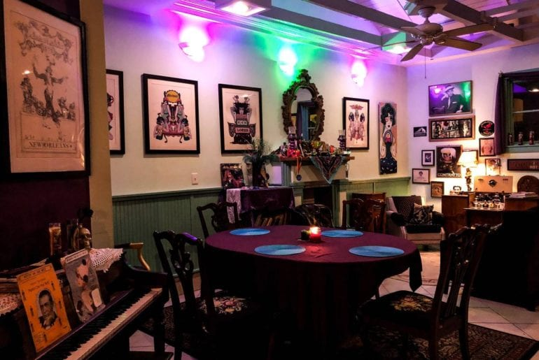 The main room is furnished with bohemian style decor and a piano.