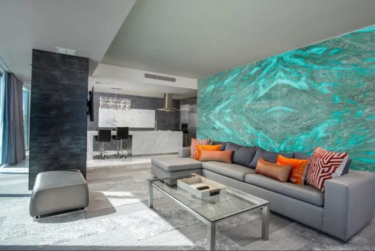 The living space has comfortable couches with orange cushions and a color changing LED wall