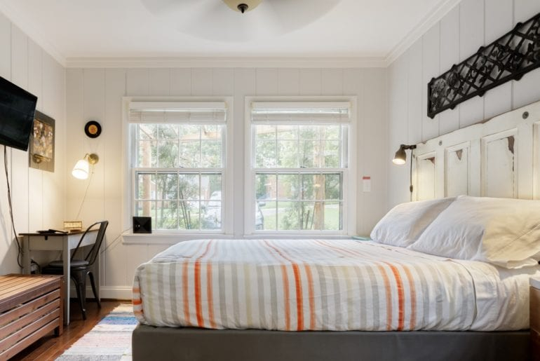 The bedroom has a queen-sized bed, a television, and a writing desk