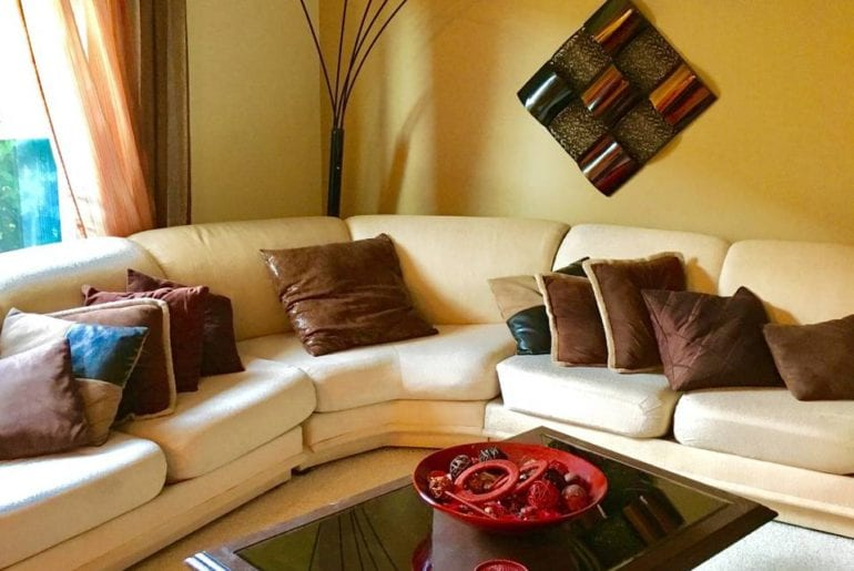 The living room has a large sectional couch and modern decor