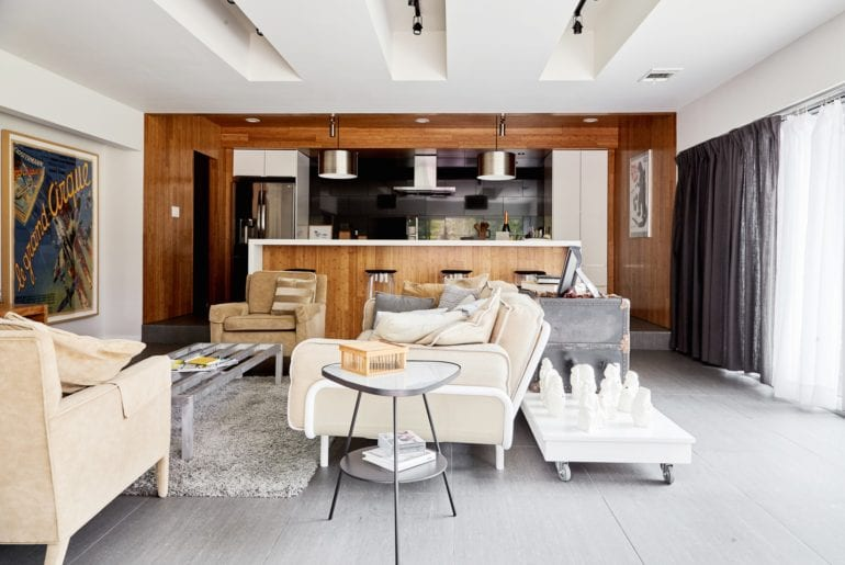 The living room features a glass wall, comfortable seating and an open kitchen.Austin Hilton
