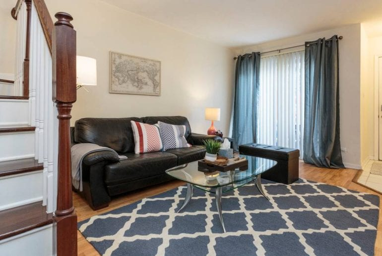Livingroom is simply decorated with a couch, a coffee table, and a blue area rug