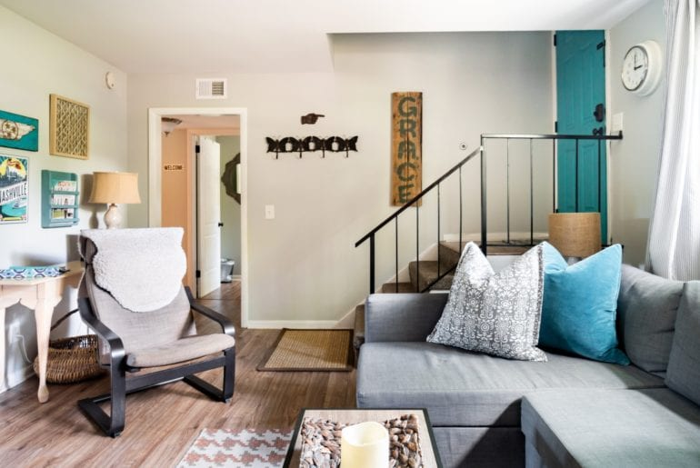 This living room has bright blue decor accents with large plush couches and a rocking chair