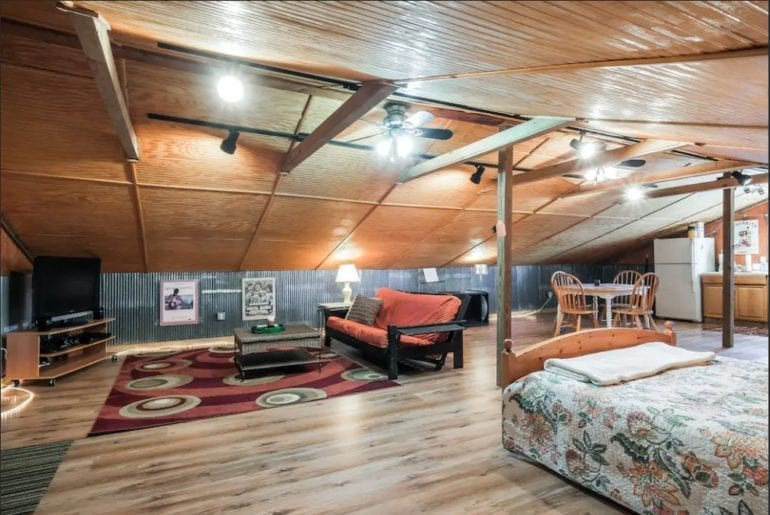 The spacious studio features wood and metal floors, walls, and ceilings for a rustic look