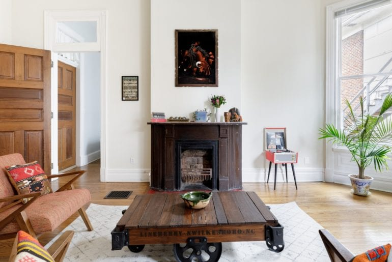 Featured in the living room is an indoor fireplace, record player, and cozy seating
