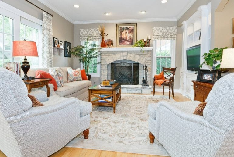 The living room has plenty of seating with an indoor fireplace and greenery.