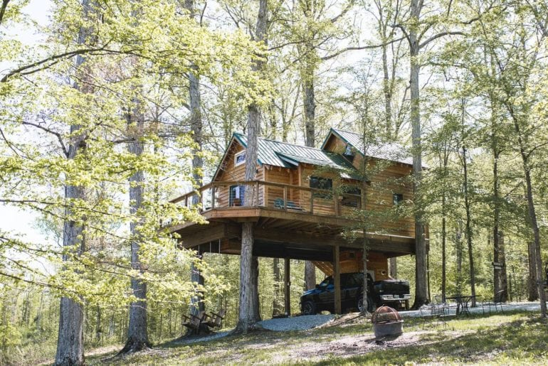 A house high in the trees. It's a wonderful unfinished wood exterior with a porch