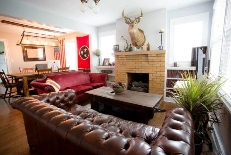 The living room has comfortable couches, a cozy fireplace, and fun decor