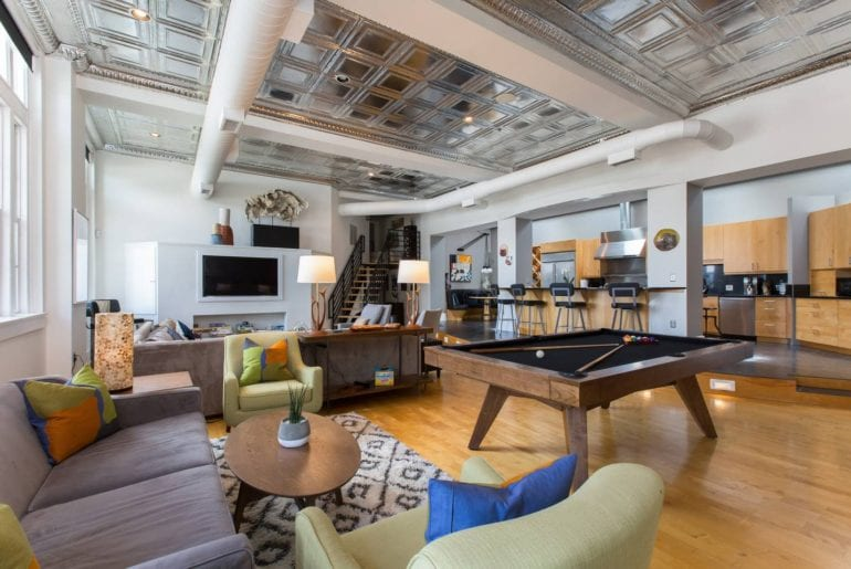 Open floor plan loft with high ceilings decorated with tin tiles is one of the best airbnbs in Asheville