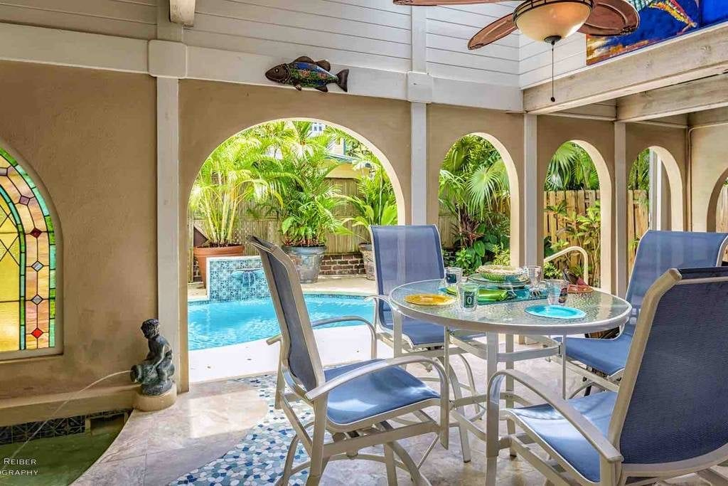 Key West property's pavilion featuring a grotto spa, patio furniture, and view of the in-ground pool with waterfall