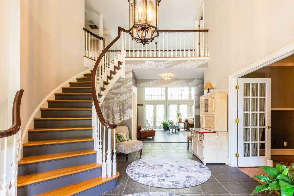 Foyer of Asheville farm house rental featuring grand staircase and contemporary wallpaper accent