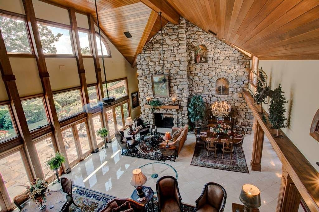Balcony view of an estate's living room featuring a stacked stone wall, and two-story, ceiling to floor windows