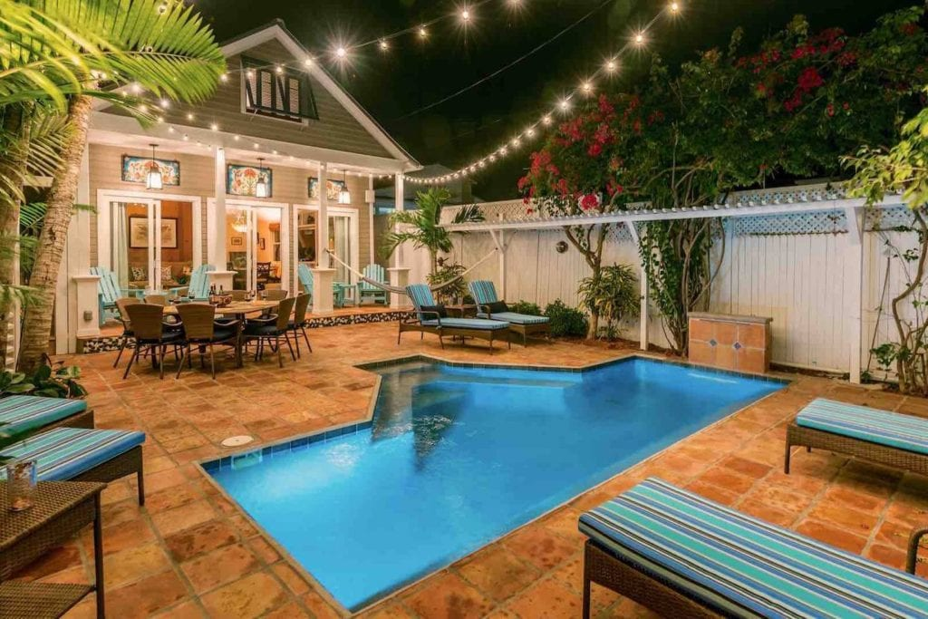 Backyard pavilion with in-ground pool, lounge chairs, and dining table lit by string lights.