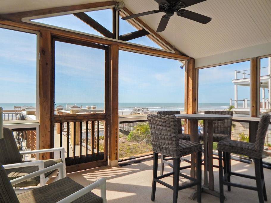 Screened-in porch features tall ceilings, a fan, a table with chairs, and a gorgeous beach view