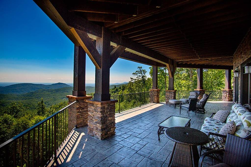 Lower deck of an Asheville rental on the edge cliff, overseeing a mountain vista