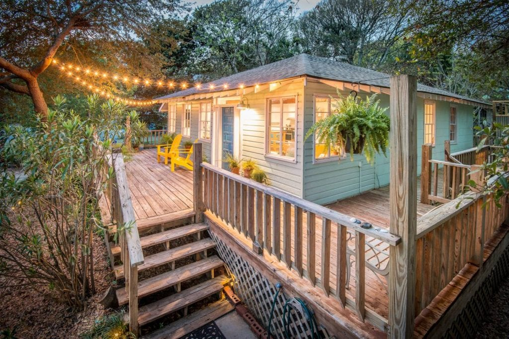 Deck of this bungalow is lit by string lights; a better alternative to Folly Beach hotels