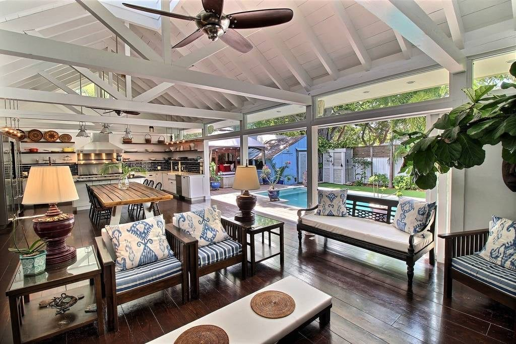 Airbnb Key West listing's open floor plan of living room and kitchen, with wide sliding doors opening right into the yard