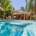 A swimming pool in front of a straw hut and some palm trees in West Palm Beach