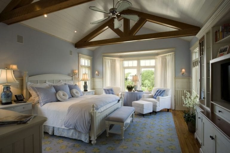 a bedroom with wooden beams in the ceiling