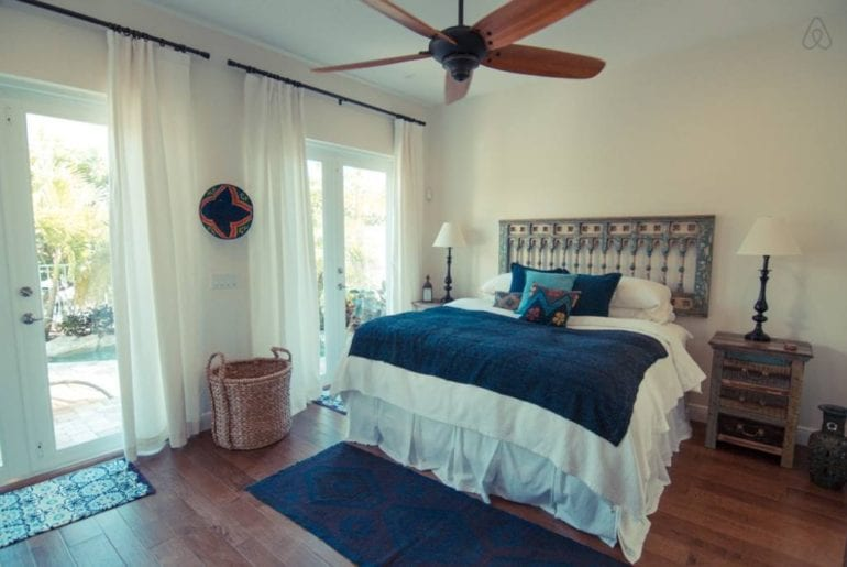 a bed with blue blanket on it and a fan above it