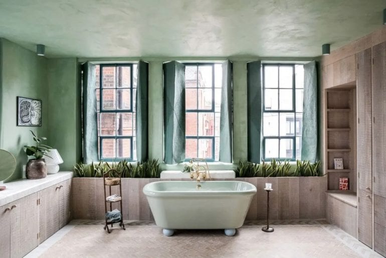 stand alone bathtub set against some large windows in London
