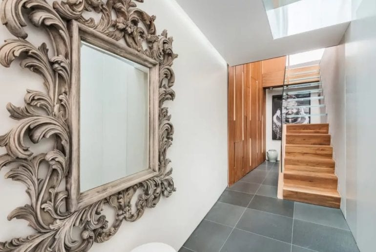 a large mirror in a frame and some wooden stairs in the background