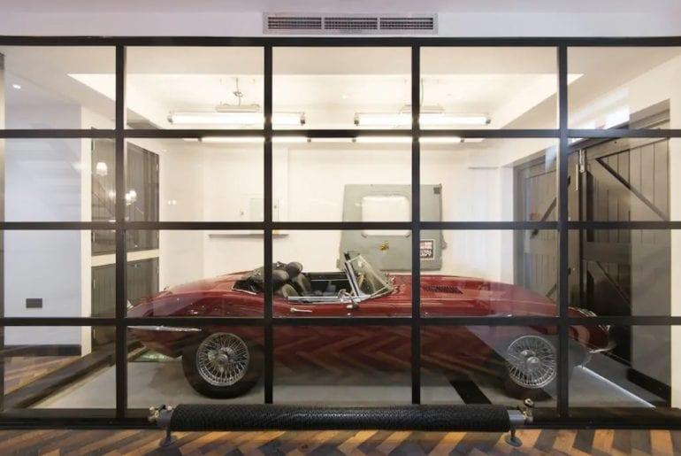 an e type jaguar in a glass garage