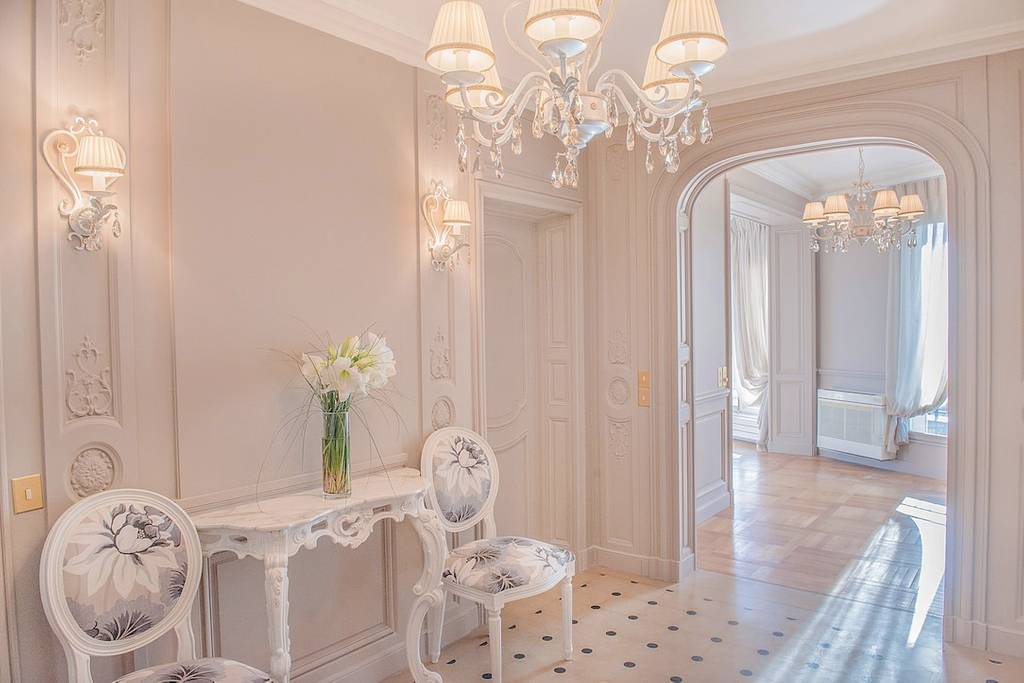 An all-white reception area with old fashioned chairs in Paris
