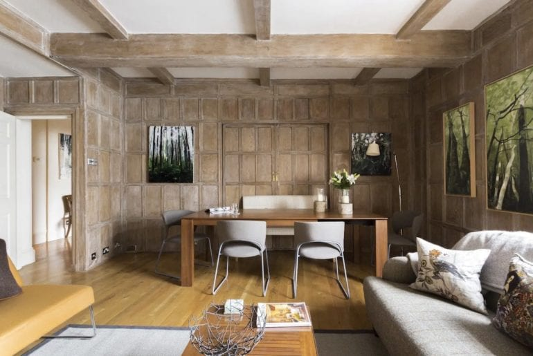 wood panelled walls and a scandinavian style dining table in a trafalgar square airbnb